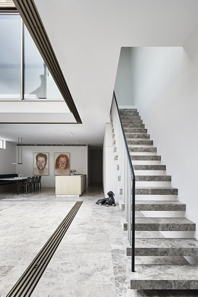 The same limestone is used for the floating stair treads, combined with painted steel balusters and a handrail of leather and steel.