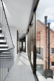 The glass addition connects to the renovated stables building via the hallway. Floors are pale-stained American oak.