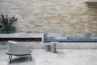 Integrated seating and firewood storage in the courtyard is crafted out of limestone at this home in Melbourne, Australia. Robson Rak Architects needed to refashion a historical cottage and stable building into a new family residence, and selected a modern palette with a long, narrow storage space for firewood.