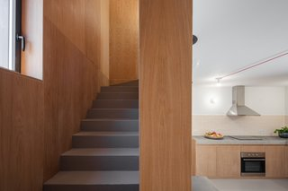 The wood-wrapped stairwell creates a sense of enclosure and warmth.