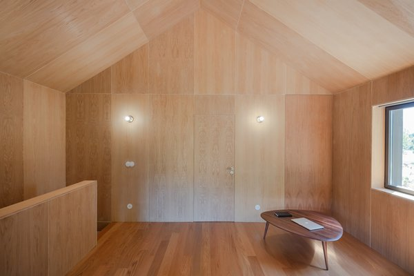 Working with a demanding budget, Filipe Pina Arquitectura added a cost-effective annex with an upper level with walls lined with exposed oak plywood.