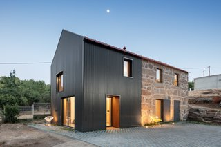 """The two-story annex is clad in charcoal corrugated steel for contrast with the granite stone and tucked under the rebuilt tile roofline. """"In materiality, the new and old were distinguished, sheltered under the same roof: the stone and the corrugated sheet, side-by-side and in continuity,"""" says the firm."""
