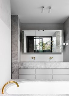 Light gray mosaic wall tile meets a pronounced slab of Natural Jeremiel Grey Marble in the vanity. The tile grid is softened by Waterstone polished plaster. The wall-mounted, brass faucets are by Vola.