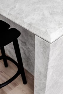"""The sculpted kitchen island bench is a true hero of the space,"" says Lynch. ""It anchors the generously scaled entertainment space while its weighty legs, honed marble finish, and soft, beveled detailing make it an artistic piece in its own right."""