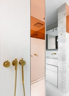 "Peach-tinted glass in the shower is an unexpected accent, yet flows with the rest of the home. ""The interior strikes a fine balance between energy and respite, boldness and refinement; an appealing and youthful space that is an expression of Tom's lifestyle and arts practice,"" says Lynch."