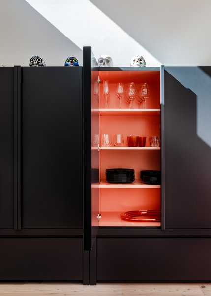 """""""The unassuming ink-toned cabinetry is lined with an unexpected burst of brilliant salmon pink; a punchy gesture that balances the strength of Tom's artworks without overshadowing them,"""" says Lynch."""
