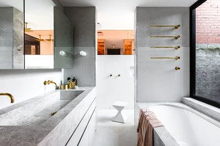 Lynch created a tactile material palette in the master bathroom, which includes plaster, tile, marble, peach-tinted glass, and natural brass.