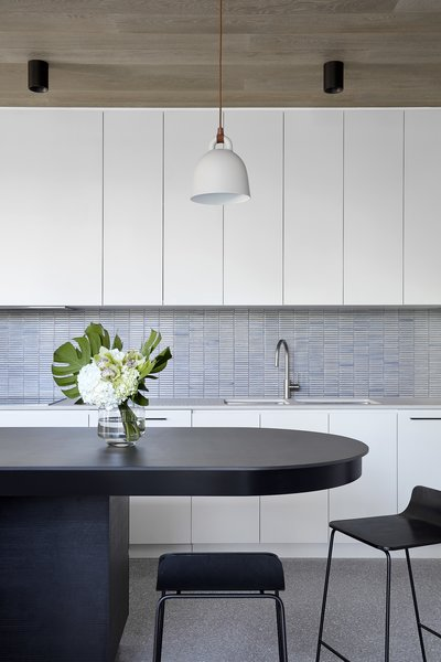 The kitchen backsplash features Yohen Border mosaic tile from Inax. Note the curved shape of the island. The stools are from Normann Copenhagen.
