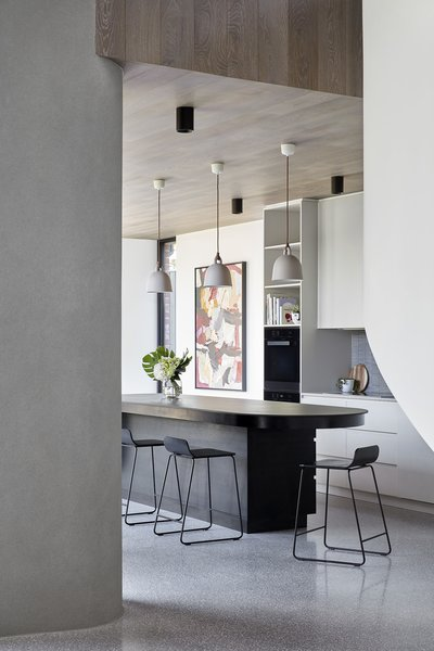Polished concrete veneer floors in French Grey from Pangaea run throughout the shared living spaces.