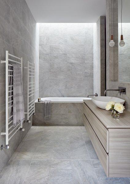 Large-format porcelain tile wraps the bathroom.