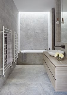 Large-format porcelain tile wraps the bathroom.