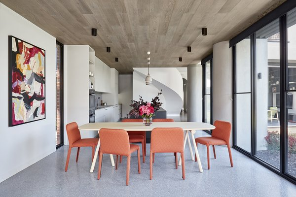 """The ceilings in the adjoining kitchen and dining room are defined by porcelain """"timber look"""" tile from Solaris. The curve of the exterior columns carries inside."""