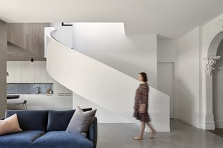 A sweeping ribbon staircase leads up to the second-floor bedrooms and rooftop deck.