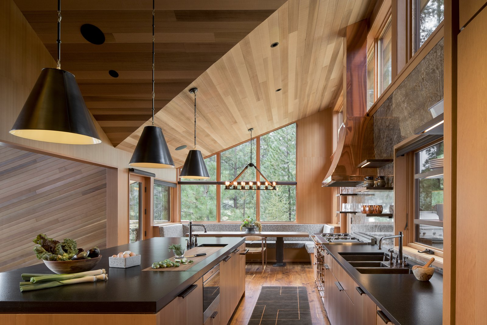 Black Butte House by Woofter Architecture wood kitchen with black granite countertops