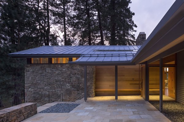 The sandstone entry court segues gracefully into a protected exterior area with a bench, creating an inviting threshold between outside and in.