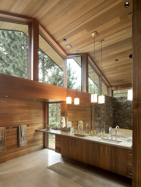The new bathroom has a walnut vanity with a limestone counter. The floors are travertine. High windows bring in plentiful natural light, glimpses of treetops, and maintain privacy.