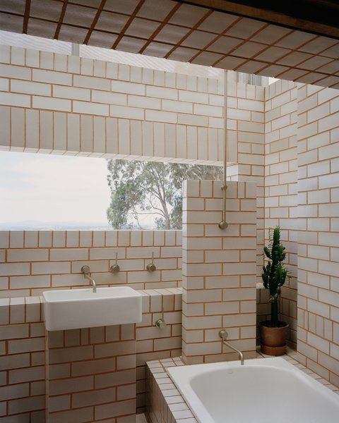 """In the bathhouse, """"clay bricks slip-glazed on two sides are laid with contrasting mortar to match the raw clay color of the other sides,"""" says the firm."""