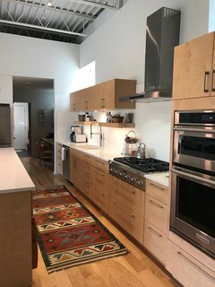 The kitchen has quartz counters, maple cabinets, a white backsplash tile with light colored grout, and glass block in the windows overlooking the alley. The hallway leads to an office niche, utility area, and the garage.
