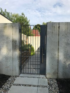 Poured-in-place concrete walls surround the courtyard and are contrasted with a steel gate designed by McCuen and painted blue-grey. The gate allows glimpses inside the garden, but doesn't compromise privacy for the residents.