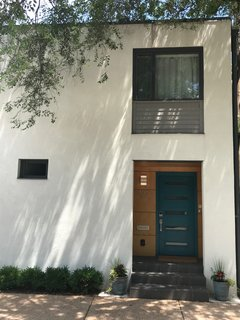The concrete block is now covered in light-colored stucco, grey lap siding, and charcoal metal trim. The front door is painted teal and surrounded by clear-coated Maple.