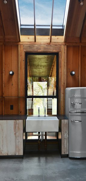 Faulkner specified a Shaws apron-front sink with separate taps for hot and cold water. It was a deliberate move to make it feel like an addition by leaving the plumbing exposed. The industrial look is complemented by steel counters and reclaimed wood cupboards. The steel-framed window opens and overlooks the screened porch, where prevailing breezes come through. A shutter can also be rolled across on the porch side for privacy.