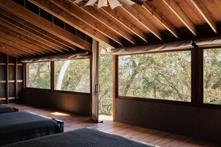 The screened porch functions as the building's primary bedroom, creating a cabin-like experience.