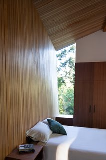 An angular window lets occupants in the bed look into the treetops.