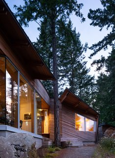 Sooke House 01 is located on a multiacre lot on the southern tip of Vancouver Island in British Columbia, surrounded by Douglas fir, Sitka spruce, and cedar trees. At the entry, Campos Studio split the roofline to accommodate an existing tree.