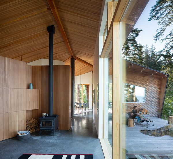 "The strips of cedar on the ceiling that fan out from the ridge beam are ""meant to evoke the canopy of the surrounding conifers,"" says the firm. The built-in cabinetry throughout is Sapele."