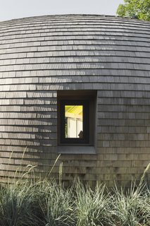 "Edwards Anker clad the home in cedar shingles in a nod to the local context, as many traditional homes on Long Island use the material. ""Because it's such an old craft, and cedar shingles have been around in Long Island for hundreds of years, they've developed technologies for double curving these shingles for a lot of curved shapes,"" says Edwards Anker."