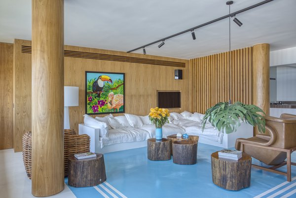 "The living room boasts a bright blue epoxy ""rug"" and tables fashioned from logs."