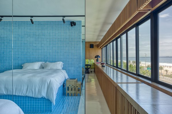 "The master suite connects to the rest of the apartment via an open walkway. ""The suite stays permanently integrated with the living room, increasing window openings and, consequently, the natural lighting and ventilation,"" says the firm. Bright blue Colortil tile covers the room—including the mattress platform—and sets it apart from the rest of the home."