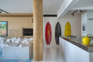 A 14-foot-long island topped with stainless steel separates the kitchen from the rest of the living area. The hallway with the surf boards leads to a second bedroom suite.