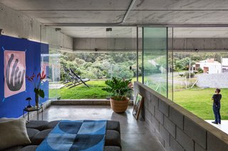 The upper bedroom opens onto a grassy balcony that's protected by a cantilevered roof.