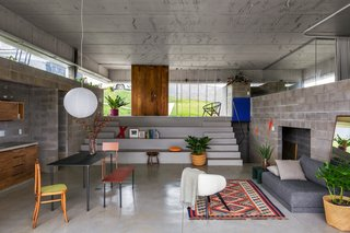 Two staircases lead from the entry to the main living space, connected by deep ledges that can function as seating or shelving.