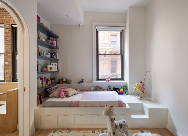 """Now, a custom built-in platform combines storage solutions with a mattress for sleeping, and doubles as a cozy, story-time nook. """"When we were creating the room for their daughter, they wanted a little magic door into her place,"""" says Klimoski, so they inserted curved pocket doors. The firm also designed the custom table lamp on the platform, made from Japanese origami paper and cast porcelain."""