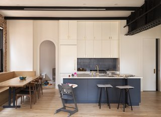 The kitchen is not visually dominant, thanks to storage that reaches to the ceiling. The backsplash tile is Ann Sacks Context tile in Metallic Black with metallic black grout, and the countertops are engineered stone. The original white oak flooring was refinished throughout the home.