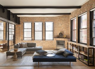 Thirteen windows in the apartment help maximize the fantastic views. The seating—including a sectional from West Elm and daybed from BoConcept—is now complemented by a fireplace specified by the firm.