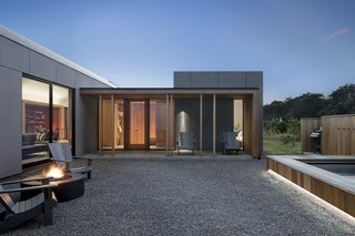 The house is broken up so that the natural site flows through the courtyard, which has a fire pit and a hot tub.