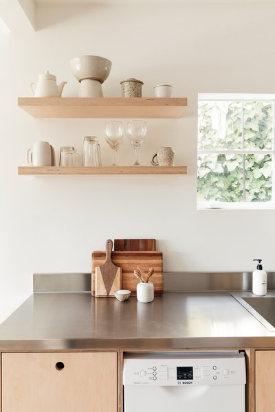 "Open shelves balance out the hard-working wall of cabinetry opposite. ""In a space like this, every fraction of an inch matters,"" says Jonathan, and making room for display and a sense of openness is also important."