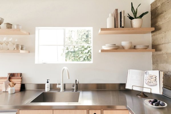 The couple installed a window over the sink to brighten up the dark basement space. The counters are stainless steel, so as to cede nicely into the concrete wall rather than compete with it.