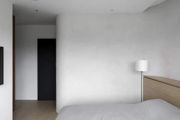 The curved wall coated in limestone softens the bedroom interior.
