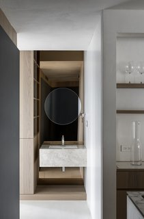 A marble-wrapped sink is mounted in a hall niche to fashion a lovely vignette at the end of a corridor.