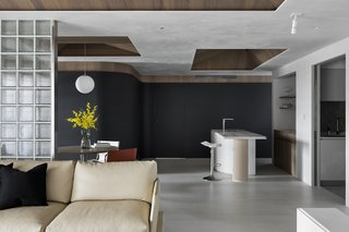 A curving charcoal wall covered in chalkboard paint lines one side of the open living area.