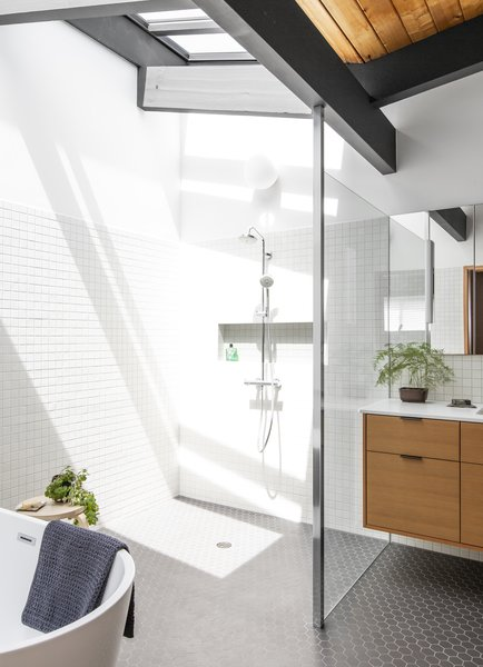 """Skylights placed between the existing eaves fill the new bathroom with light. """"That was a moment where we thought that we could tie in our changes to the house seamlessly with the old design,"""" says Marsh. """"When the light goes over the skylight, it creates different shadow lines."""""""