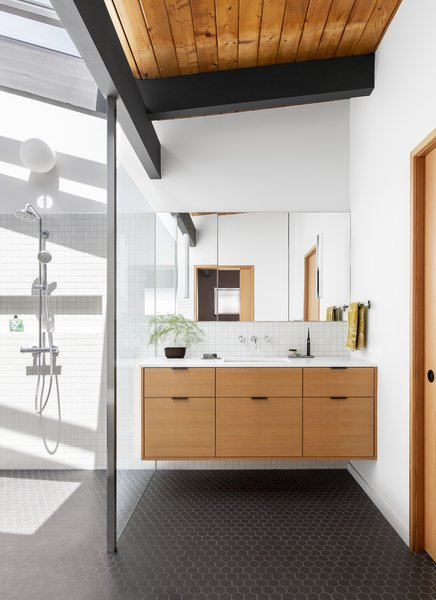 The bathroom features simple black hex tile on the floor and white tile laid in a grid on the walls. The custom vanity is fir, in keeping with the rest of the home's material palette.