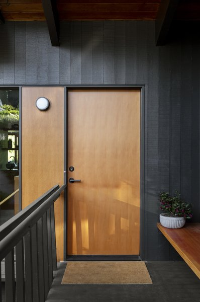 In the remodel, the façade was touched up, the front door replaced, and an entry bench installed.