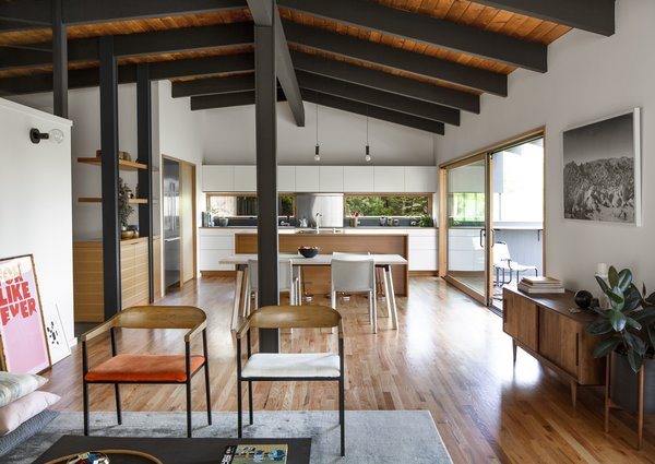 Removing the wall helps to expose the home's beautiful post and beam structure throughout and unify the living spaces. To emphasize the structure, the team repainted the ceiling beams a dark color to contrast with the natural wood that was preserved.