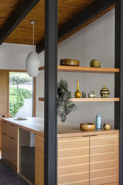 The architects also removed a wall and replaced it with low casework and built-in shelves slotted between the posts. This allows light to flow through the entry and gives the owners an opportunity to display their ceramics collection.
