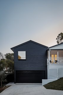 A new garage is topped with a master suite and clad in James Hardie Scyon Linea boards painted a dark color, Dulux Monument.